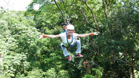 European woman flying in the jungle at canopy tour Footage