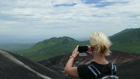 European woman takes pictures with mobile from Cerro Negro vulcano Footage