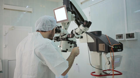 Doctor loking at monitor at big microscope system in a hospital laboratory Footage