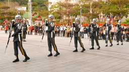 Six guards synchronously rotate rifles in hand, part of ceremony Bild
