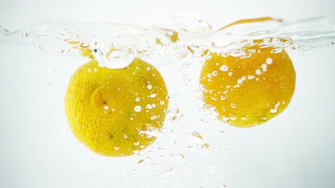 Two Tangerines Being Thrown into Water in Ultra Slow Motion Footage