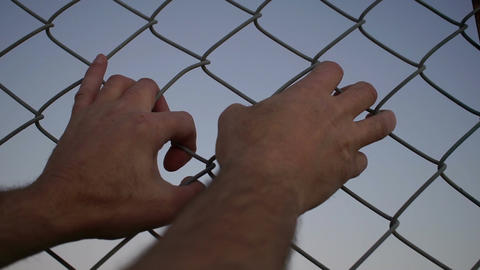 Both Hands Grabbing Chain Link Fence stock footage