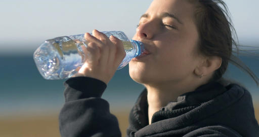 Drinking fresh water from a plastic bottle young adult model woman girl Footage