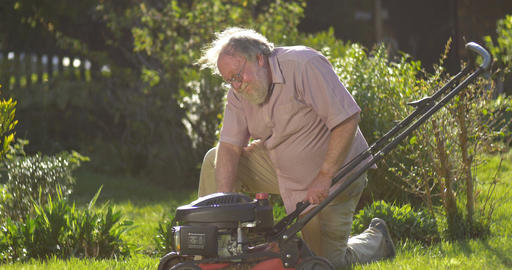 Retired elderly man mowing lawn enjoying retirement Live Action