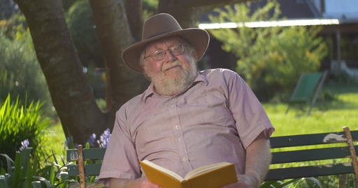 Retired elderly man relaxing outdoors reading a book enjoying retirement Live Action