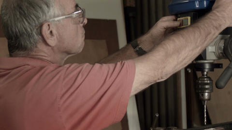 Man working indoors in hobby shed or workshop with carpentry power drill tools Footage