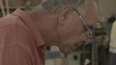 Retired Man 50s-60s working indoors in hobby shed or workshop with carpentry pow Footage