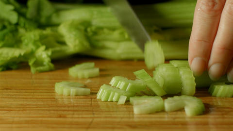 healthy fresh celery food prep cutting up of vegetables and fruit in kitchen Footage