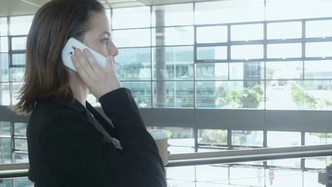 Slow motion businesswoman walking in office building talking on phone Footage
