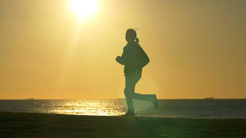 Person jogging exercising in park with sun behind slowmo Footage