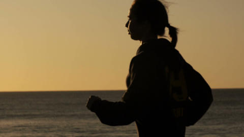 Outdoors fitness runner woman running by beach exercising slow motion Footage