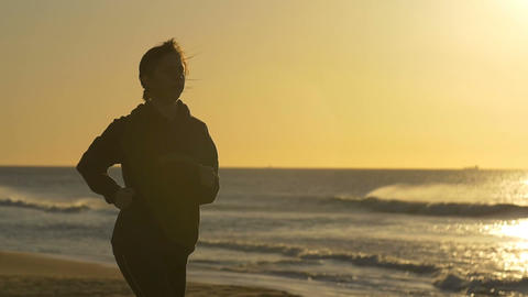 Person jogging exercising by beach with sun behind slowmo Footage