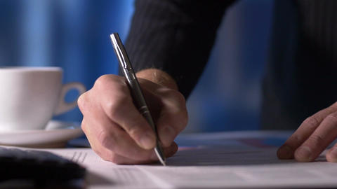 Businessman looking at documents signing paperwork in office at desk GIF