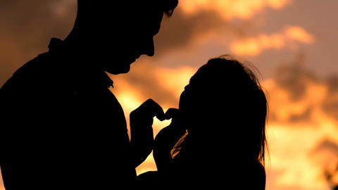 Romantic young couple in love making a heart shape with their hands silhouette Footage