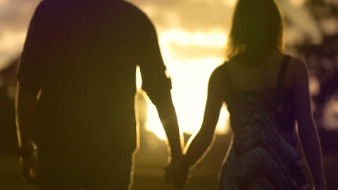 Young couple in loving relationship holding hands walking sunset lifestyle Footage