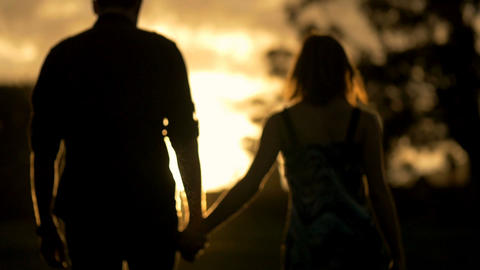 Young couple in love holding hands walking into sunset Footage