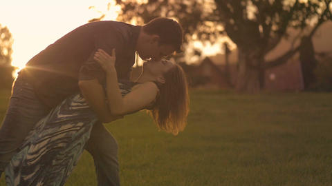 Beautiful Young Couple in Love embrace and kiss outdoors in park Footage