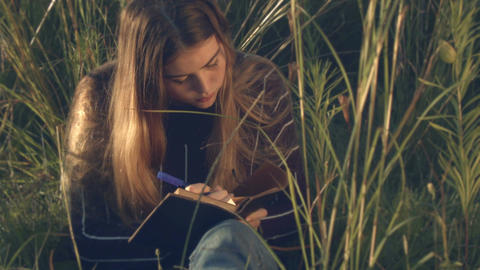 young teenage girl writing in diary putting down her thoughts Footage