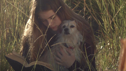 young teenage girl with dog reading book relaxing outdoors Footage