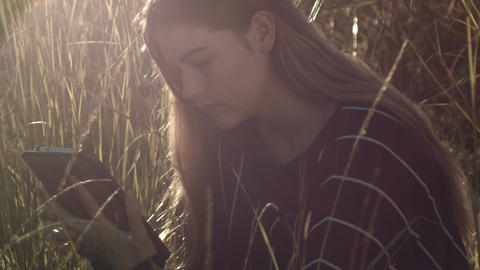 young teenage girl on ipad tablet inteacting with social media outdoors in sun Live Action