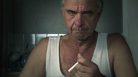 Adult male holding cigarette attempting to quit smoking at table Footage