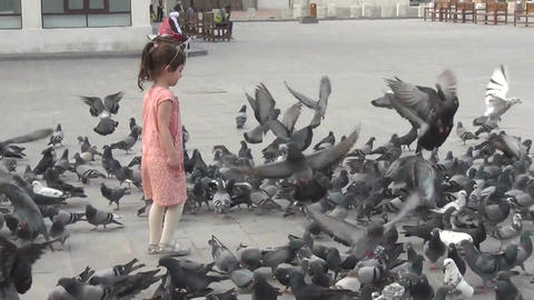 Little girl playing with pigeons on square Footage