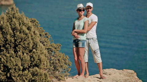 Couple hugging on the background of rocks and the sea on a hot day Footage