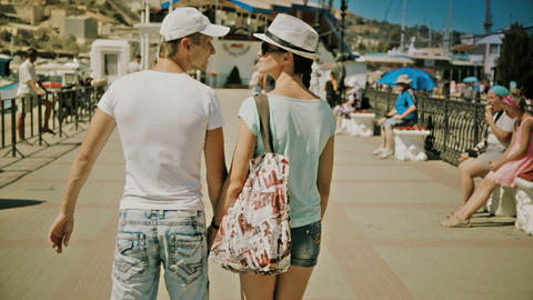 happy couple holding hands on a walk while on vacation Footage