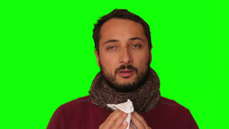 A cold man sneezes in a tissue Green Screen Footage